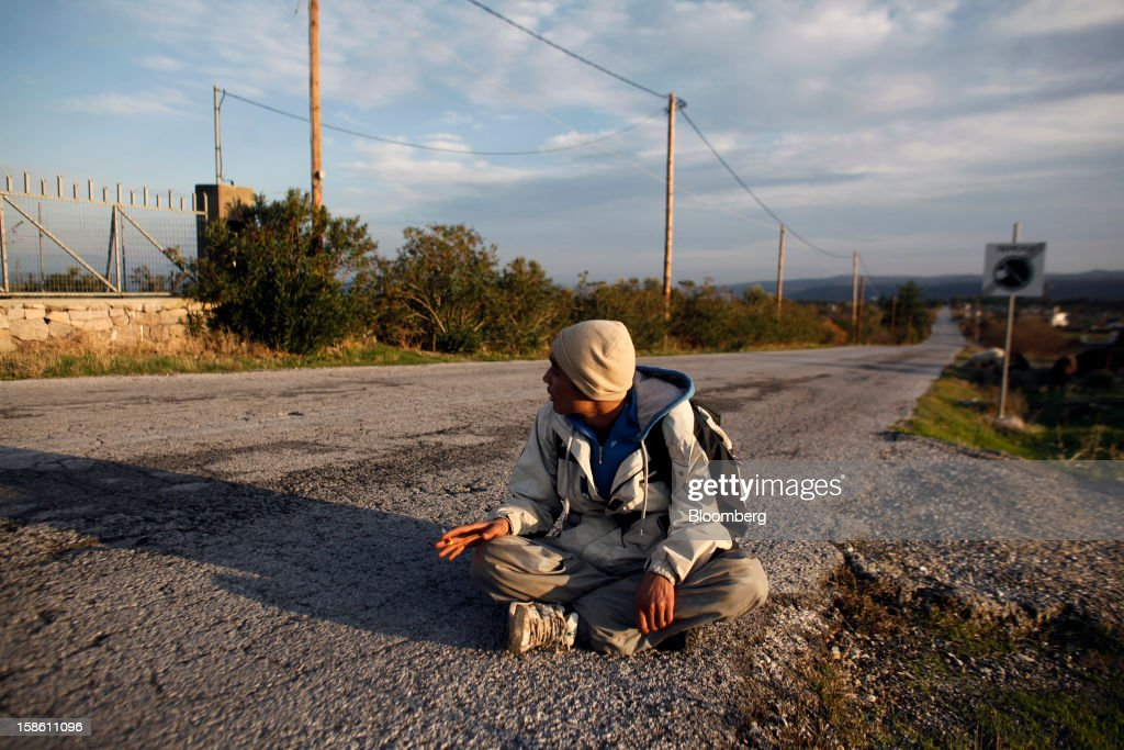 Houssein, a 20-year-old Afghan immigrant, rests on the roadside during a walk to the town of Mytilene hours after he and other refugees arrived by boat from Turkey in the northern part of the island of Lesbos, Greece, on Saturday, Dec. 8, 2012. In recent months, Lesbos has become a hot spot for migrants as Greece struggles to cope with waves of refugees from Middle Eastern conflict even as it reels from economic crisis at home. Photographer: Kostas Tsironis/Bloomberg via Getty Images