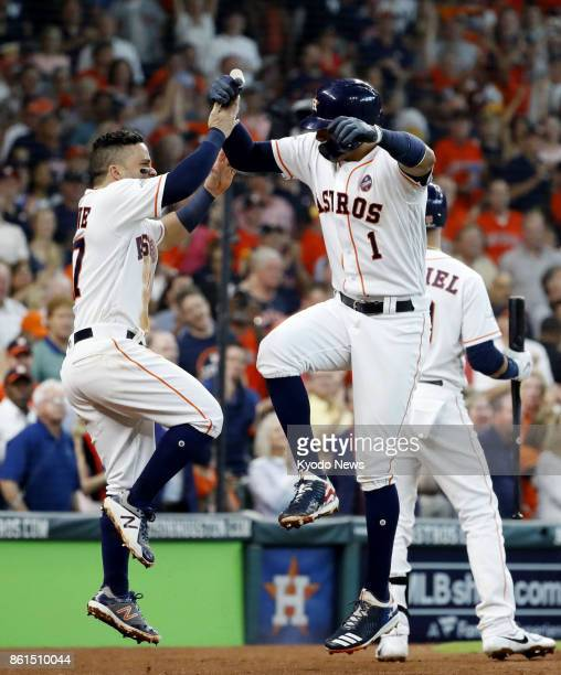 Houston Astros' Carlos Correa celebrates with his teammate Jose Altuve after hitting a home run in the fourth inning of an American League...