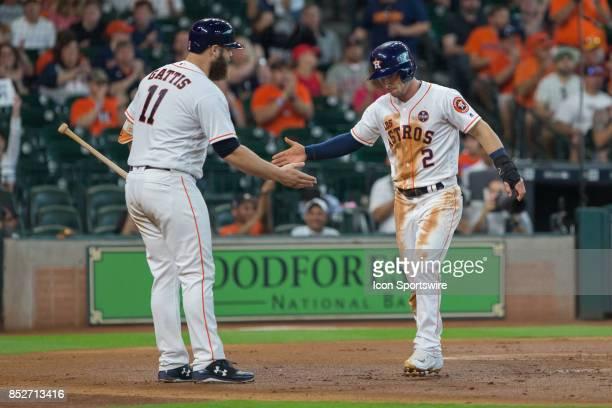 Houston Astros catcher Evan Gattis shakes hands with Houston Astros third baseman Alex Bregman scoring on a line single from Houston Astros shortstop...