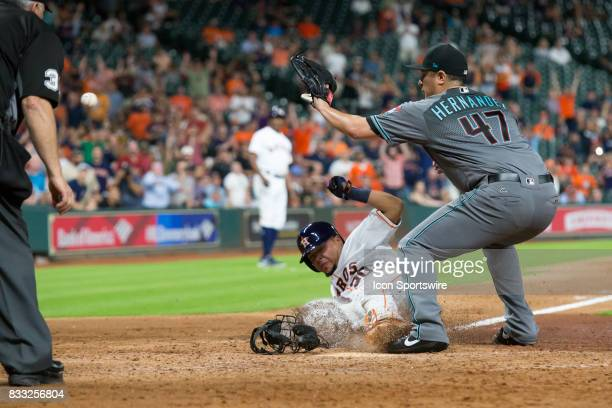 Houston Astros catcher Juan Centeno scores on a passed by thrown by Arizona Diamondbacks relief pitcher David Hernandez in the eighth inning of a MLB...
