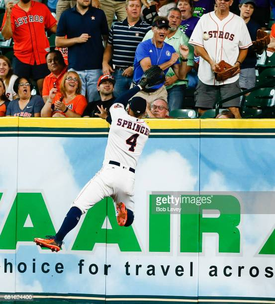Houston Astros center fielder George Springer leaps at the wall but unable to catch a home run by Atlanta Braves third baseman Adonis Garcia in the...