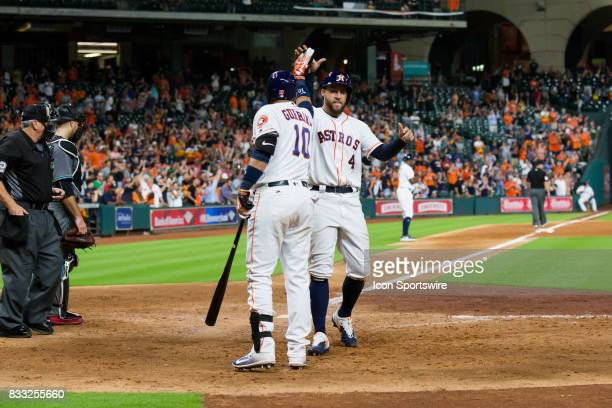 Houston Astros center fielder George Springer shakes hands with Houston Astros first baseman Yuli Gurriel after scoring in the eighth inning of a MLB...