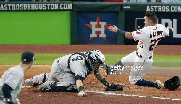 Houston Astros' Jose Altuve scores a run on Carlos Correa's double while New York Yankees catcher Gary Sanchez tries to pick up the ball in the ninth...