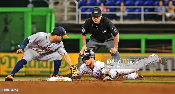 Houston Astros' Jose Altuve tags out Miami Marlins' JT Riddle at second base in the third inning on Monday May 15 2017 at Marlins Park in Miami Fla