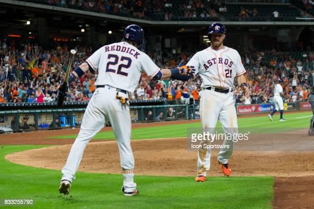 Houston Astros left fielder Derek Fisher shakes hands with Houston Astros right fielder Josh Reddick after hitting a homerun in the eighth inning of...