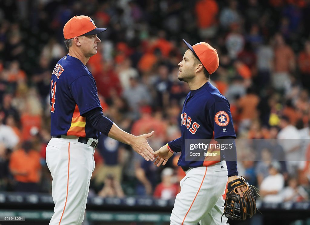 Houston Astros manager A.J. Hinch greets Jose Altuve #27 after the Astros beat the Detroit Tigers 5-4 at Minute Maid Park on April 17, 2016 in Houston, Texas.