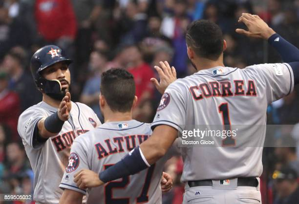 Houston Astros Marwin Gonzalez celebrates with teammates Jose Altuve and Carlos Correa after he scored from Carlos Beltran double in the ninth inning...