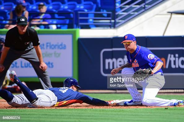 Houston Astros outfielder George Springer beats a pickoff play as New York Mets infielder Wilmer Flores prepares to tag during a Spring Training game...