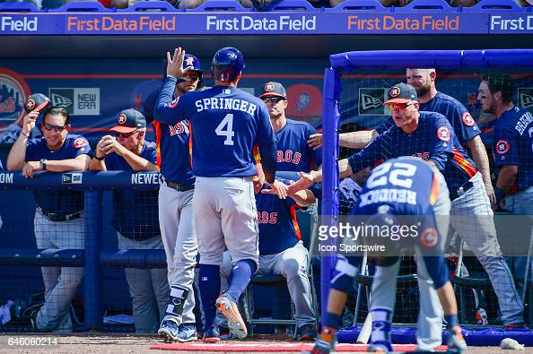 Houston Astros outfielder George Springer is congratulated by teammates in the dugout after scoring during a Spring Training game between the Houston...