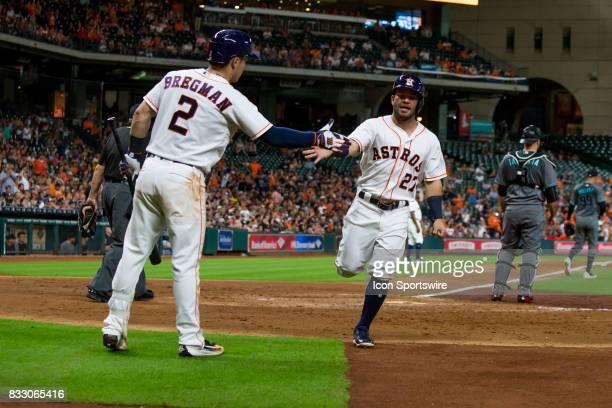 Houston Astros second baseman Jose Altuve scores on a sacrifice hit gets highfives by Houston Astros third baseman Alex Bregman in the third inning...