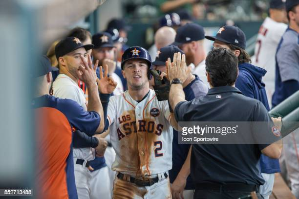 Houston Astros third baseman Alex Bregman shakes hands in the dugout after scoring on a line single from Houston Astros shortstop Carlos Correa in...