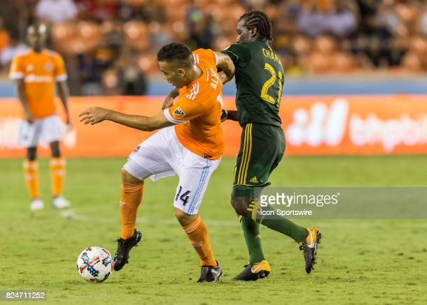 Houston Dynamo midfielder Alex fights to keep the ball away from Portland Timbers midfielder Diego Chara during the MLS match between the Portland...