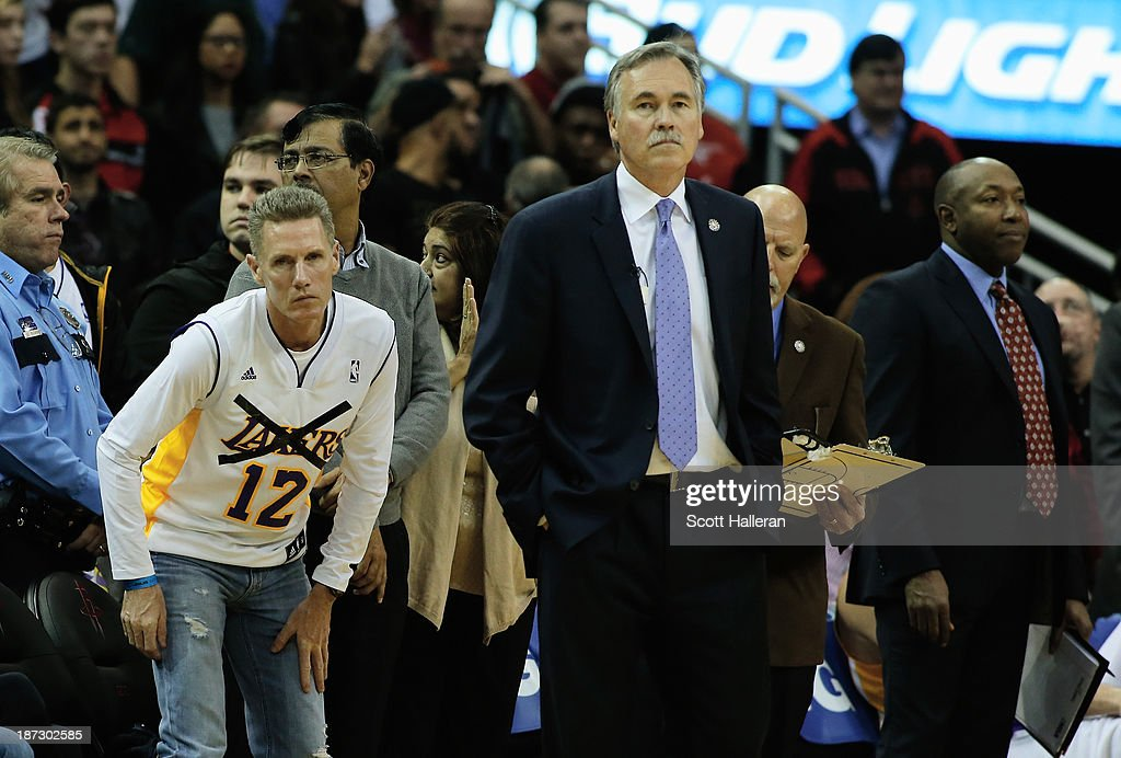 A Houston Rockets fan watches a break in the action alongside the bench and Los Angeles Lakers head coach <a gi-track='captionPersonalityLinkClicked' href=/galleries/search?phrase=Mike+D%27Antoni&family=editorial&specificpeople=203175 ng-click='$event.stopPropagation()'>Mike D'Antoni</a> during the game at Toyota Center on November 7, 2013 in Houston, Texas.