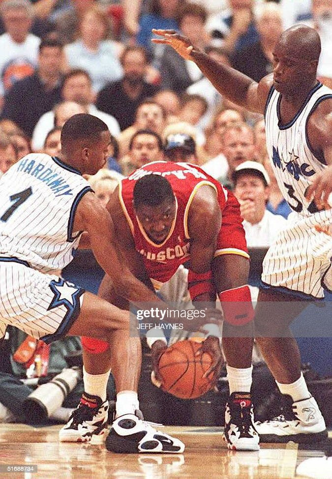 Houston Rockets Hakeem Olajuwon (C) fights for control of the ball against Orlando Magic's Shaquille O'Neal (R) and Anfernee Hardaway (L) 09 June during the first half of game two of the NBA Championships in the Orlando Arena in Florida.