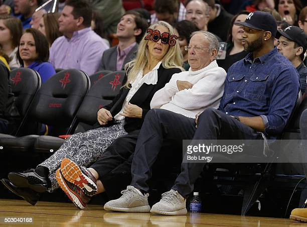 Houston Rockets owner Les Alexander center sits with former Houston Rocket Tracy McGrady at Toyota Center on December 31 2015 in Houston Texas NOTE...