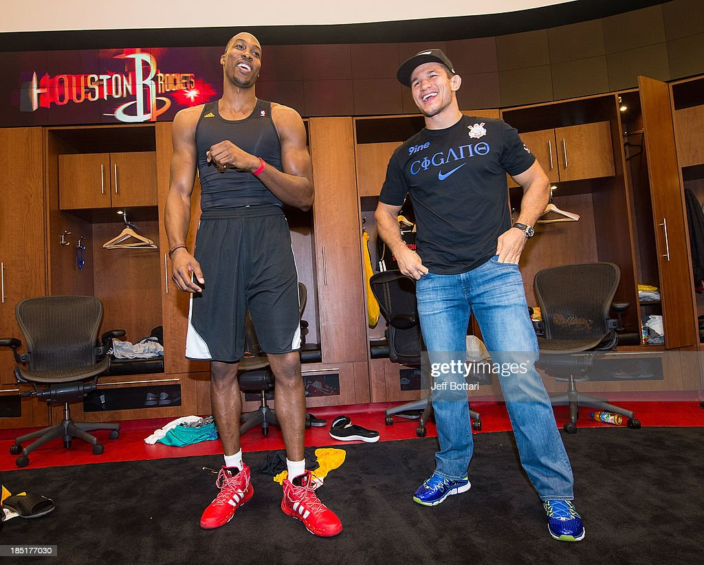 Houston Rockets player <a gi-track='captionPersonalityLinkClicked' href=/galleries/search?phrase=Dwight+Howard&family=editorial&specificpeople=201570 ng-click='$event.stopPropagation()'>Dwight Howard</a> and UFC fighter <a gi-track='captionPersonalityLinkClicked' href=/galleries/search?phrase=Junior+Dos+Santos&family=editorial&specificpeople=6312675 ng-click='$event.stopPropagation()'>Junior Dos Santos</a> interact in the Houston Rockets locker room during the UFC 166 Ultimate Media Day at the Toyota Center on October 16, 2013 in Houston, Texas.