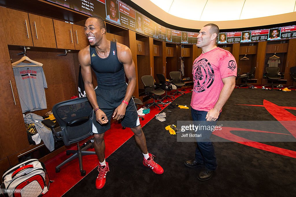 Houston Rockets player <a gi-track='captionPersonalityLinkClicked' href=/galleries/search?phrase=Dwight+Howard&family=editorial&specificpeople=201570 ng-click='$event.stopPropagation()'>Dwight Howard</a> laughs as he faces off against UFC Heavyweight Champion <a gi-track='captionPersonalityLinkClicked' href=/galleries/search?phrase=Cain+Velasquez&family=editorial&specificpeople=5445619 ng-click='$event.stopPropagation()'>Cain Velasquez</a> in the Houston Rockets locker room during the UFC 166 Ultimate Media Day at the Toyota Center on October 16, 2013 in Houston, Texas.