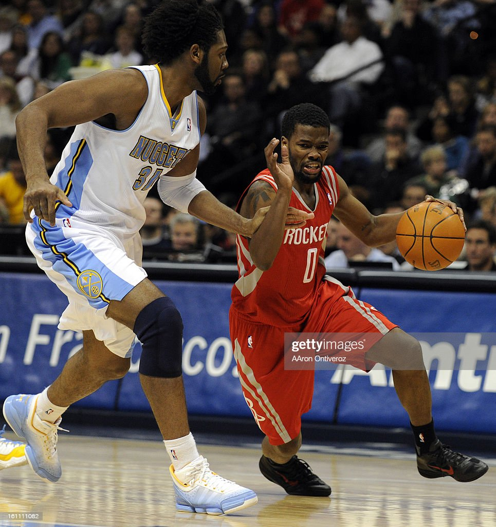 Houston Rockets point guard Aaron Brooks (0) drives past Denver Nuggets center Nene (31) during the second quarter on Monday, January 3, 2011 at the Pepsi Center. AAron Ontiveroz, The Denver Post