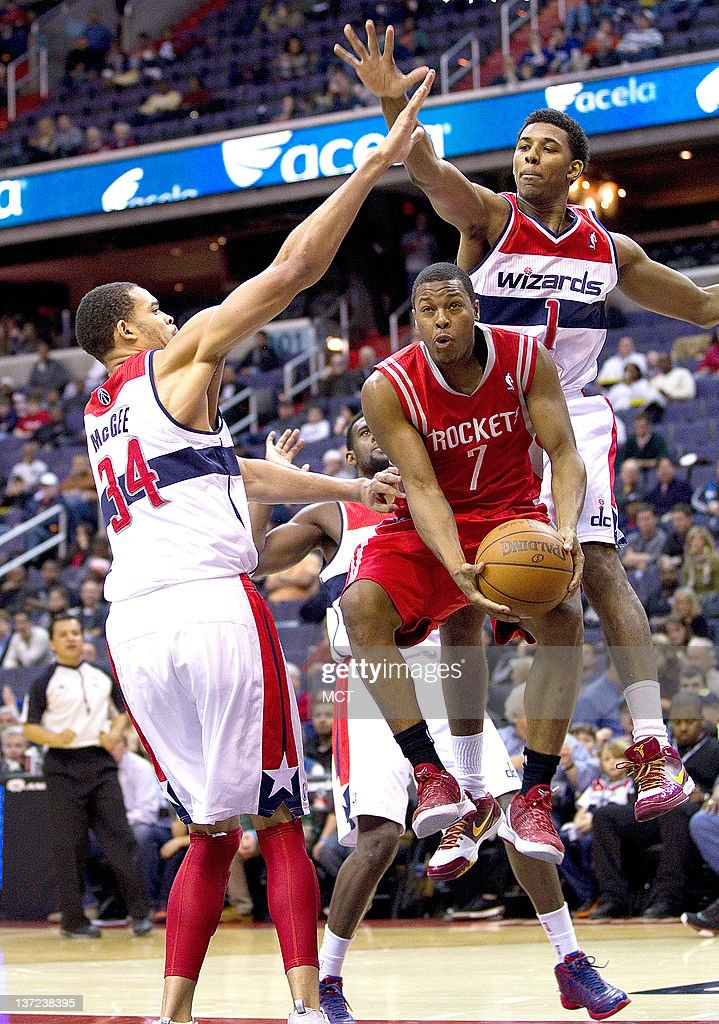Houston Rockets point guard Kyle Lowry (7) is fouled by Washington Wizards shooting guard Nick Young (1) and center JaVale McGee (34) during their game played at the Verizon Center in Washington, D.C., Monday, January 16, 2012.
