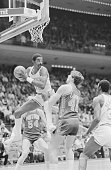 Rocket's power forward Ralph Sampson leaps into the air to pull down a rebound as the Pistons' center Bill Laimbeer looks on during first quarter...