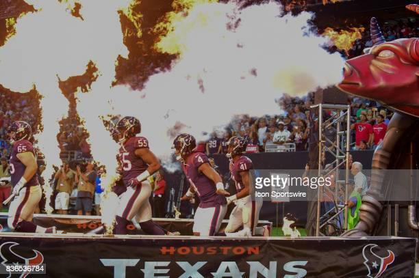 Houston Texans quarterback Deshaun Watson flies through the fire as he enters the field before the NFL preseason game between the New England...