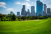 Houston Texas green open park perfect sunny day at Buffalo Bayou River Park with downtown skyline cityscape in background with tall towers and skyscrapers