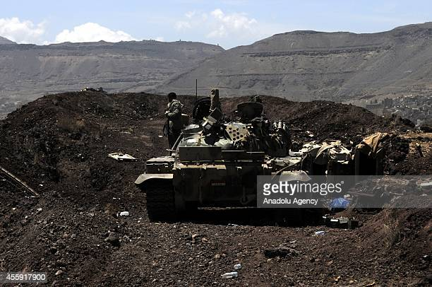 Houthi militant waits near a seized tank after they captured the headquarters of the Sixth Military Zone following rough clashes with Yemeni...