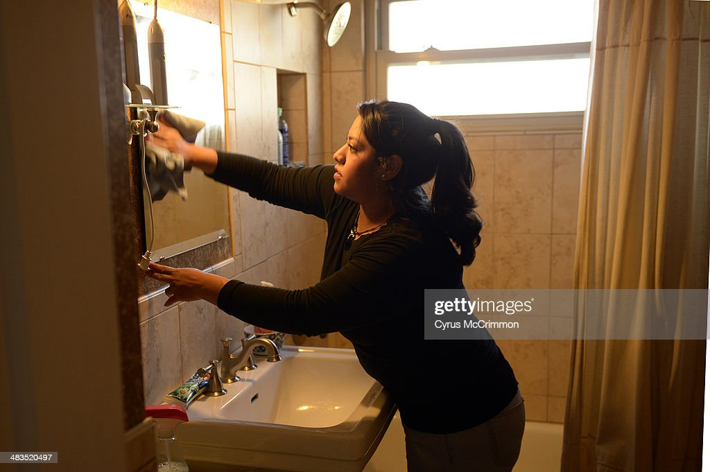 How to hire a housecleaning service for your home. Yareli Gonzalez of Wendy's Cleaning Service cleans a bathroom mirror as she cleans a home in Denver on Tuesday, April 8, 2014.
