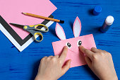 How to make envelope in form of bunny for Easter greetings. Children's art project. DIY concept. Step by step photo instruction. Step 9. Glue bunny eyes