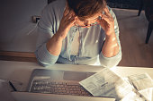 Stressed mature woman having a headache while playing bill online at home.