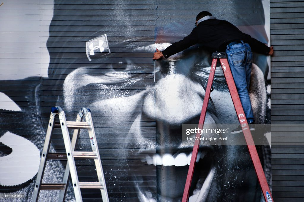 Howard Carrasco of 7M Graphix hangs a mural of Baltimore Raven Ray Lewis onto a garage door Wednesday February 14, 2013 in Baltimore, MD in the Harbor East neighborhood.