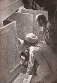 Howard Carter and associates opening the doors of King Tutankhamun's burial shrine in the Valley of the Kings Egypt screen print from a photograph...