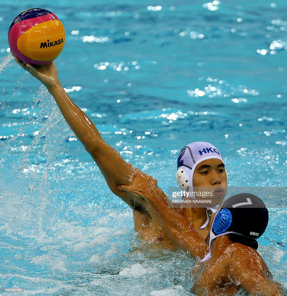 Howard Cheng (L) of Hong Kong tries to protect the ball from Yusuke Shimizu of Japan during the two teams water polo game in at the 9th Asian Swimming Championships in Dubai, on November 21, 2012.