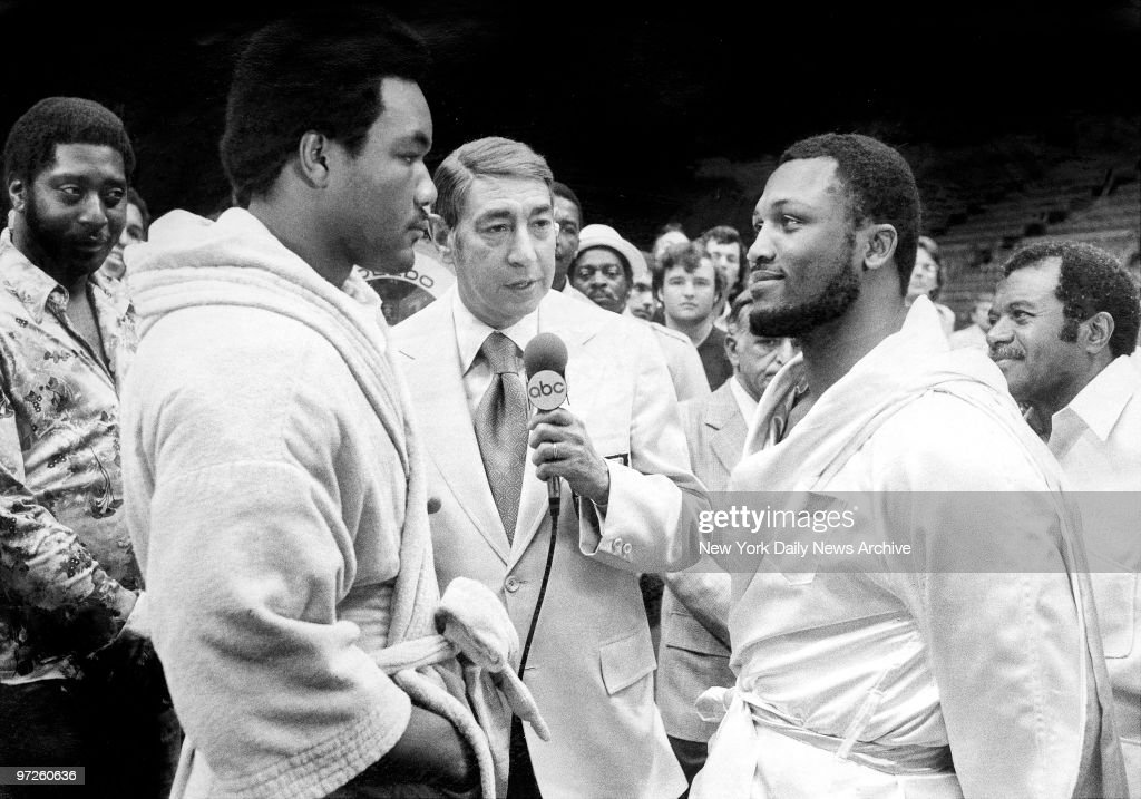 Howard Cosell (center) looks on as George Foreman and Joe Frazier engage in a staring match at weigh-in for their June 15 bout.