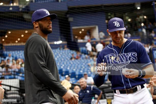 J Howard of the Tampa Bay Buccaneers hands an autographed baseball to Evan Longoria of the Tampa Bay Rays moments before throwing out the ceremonial...