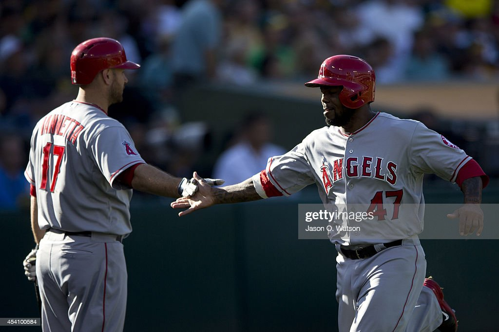<a gi-track='captionPersonalityLinkClicked' href=/galleries/search?phrase=Howie+Kendrick&family=editorial&specificpeople=628938 ng-click='$event.stopPropagation()'>Howie Kendrick</a> #47 of the Los Angeles Angels of Anaheim is congratulated by <a gi-track='captionPersonalityLinkClicked' href=/galleries/search?phrase=Chris+Iannetta&family=editorial&specificpeople=836137 ng-click='$event.stopPropagation()'>Chris Iannetta</a> #17 after scoring a run against the Oakland Athletics during the second inning at O.co Coliseum on August 24, 2014 in Oakland, California.
