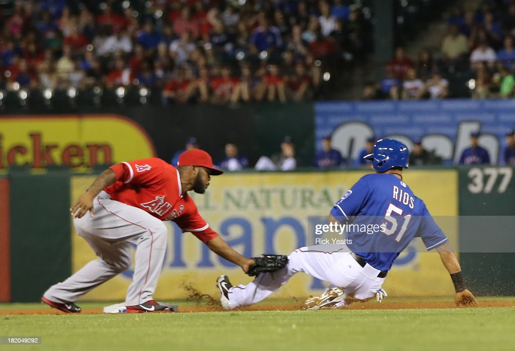 <a gi-track='captionPersonalityLinkClicked' href=/galleries/search?phrase=Howie+Kendrick&family=editorial&specificpeople=628938 ng-click='$event.stopPropagation()'>Howie Kendrick</a> #47 of the Los Angeles Angels of Anaheim tags out <a gi-track='captionPersonalityLinkClicked' href=/galleries/search?phrase=Alex+Rios&family=editorial&specificpeople=224676 ng-click='$event.stopPropagation()'>Alex Rios</a> #51 of the Texas Rangers after he grounded into a fielder's choice in the first inning at Rangers Ballpark in Arlington on September 27, 2013 in Arlington, Texas.