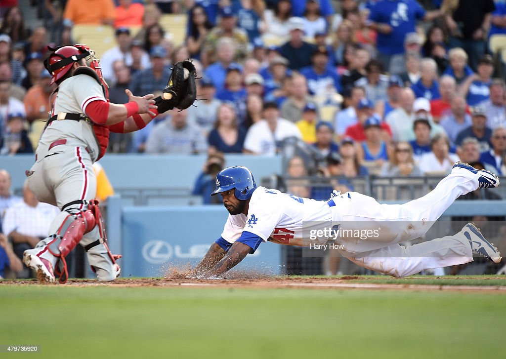Howie Kendrick of the Los Angeles Dodgers slides ahead of a tag from Carlos Ruiz of the Philadelphia Phillies to score on a sacrifice fly taking a 10...