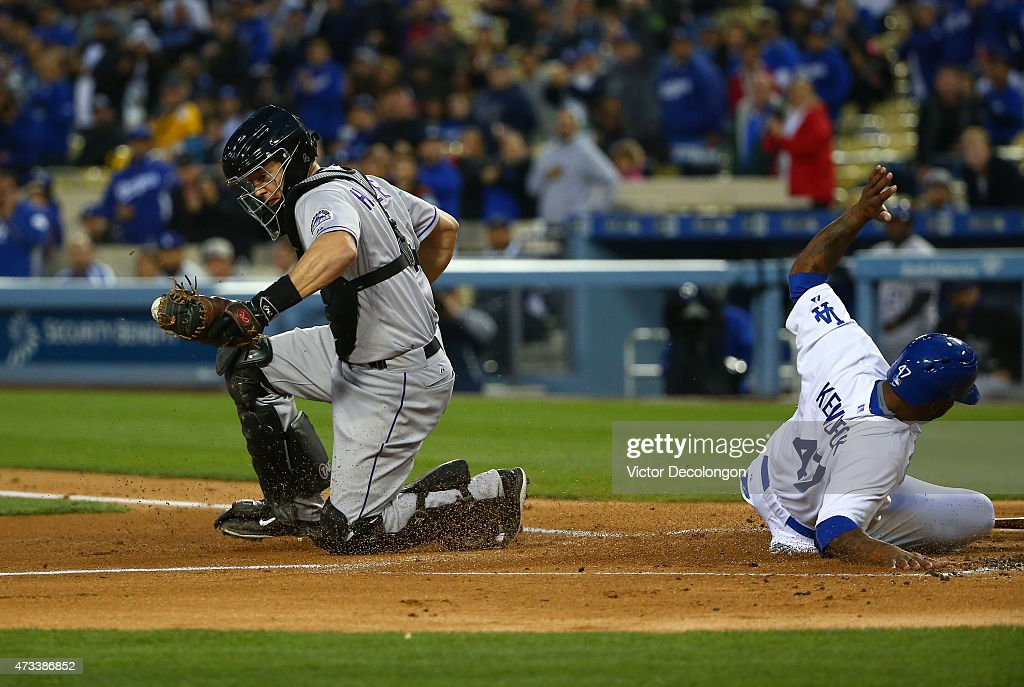 Howie Kendrick #47 of the Los Angeles Dodgers slides into home plate safely to score past catcher Nick Hundley #4 of the Colorado Rockies in the first inning during the MLB game at Dodger Stadium on May 14, 2015 in Los Angeles, California. Kendrick scored on a two-run RBI double by teammate Adrian Gonzalez.