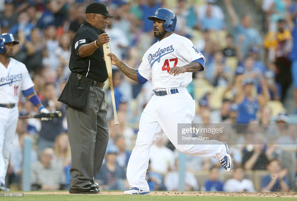 Howie Kendrick of the Los Angeles Dodgers takes Yasmani Grandal's bat from home umpire Laz Diaz as he scores a run on Grandal's single in the second...