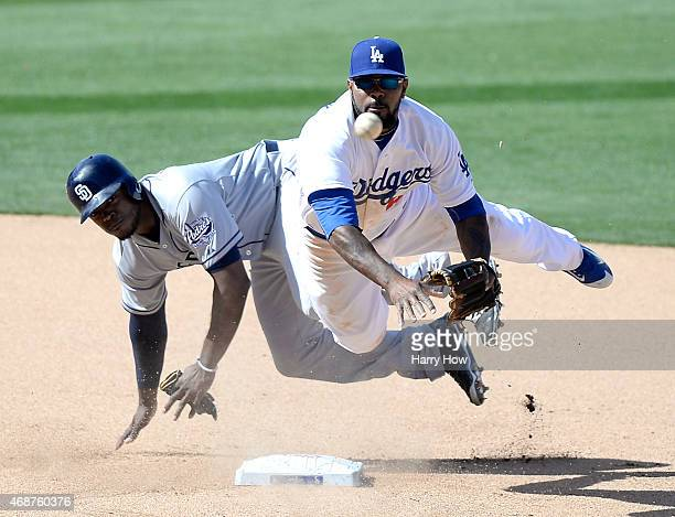 Howie Kendrick of the Los Angeles Dodgers turns a double play over Justin Upton of the San Diego Padres in the eighth inning during opening day at...