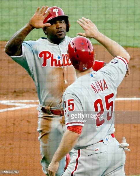Howie Kendrick of the Philadelphia Phillies and Daniel Nava celebrate after scoring in the first inning against the Boston Red Sox at Fenway Park on...