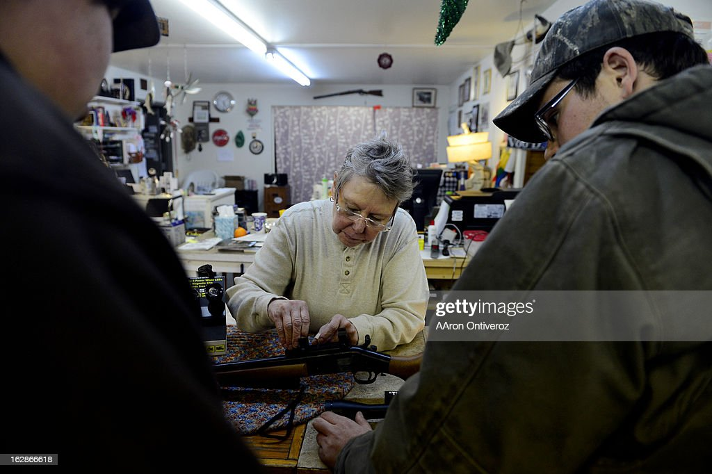 Howllowpoint Gun Shop Owner Erin Jerant helps mount a scope on a hunting rifle for Justin Noga (right) as friend Ricky Kelly looks on in Walsenburg. Jerant says she has known the two since they were young enough to sit on the store's countertops. Gun owners in southern Colorado largely agree that responsible ownership begins at home.