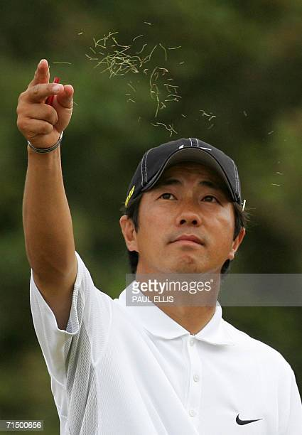 Keiichero Fukabori of Japan throws grass in the air to test the direction of the wind as he plays in the third round of the 135th British Open Golf...