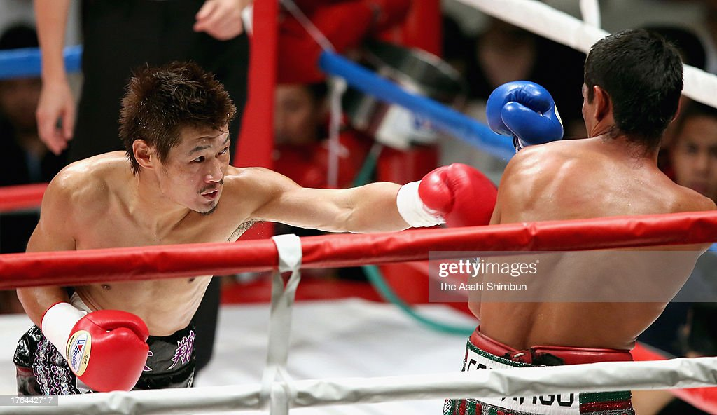 Hozumi Hasegawa of Japan hits Genaro Camargo of Mexico in a non-title match at the Ota-City General Gymnasiumon on August 12, 2013 in Tokyo, Japan. Hasegawa scored a first round knockout over Camargo.