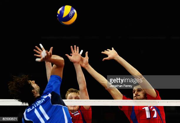 Hristo Zlatanov of Italy smashes as Sergey Grankin and Alexander Volkov of Russia block in the Bronze Medal volleyball match between Russia and Italy...