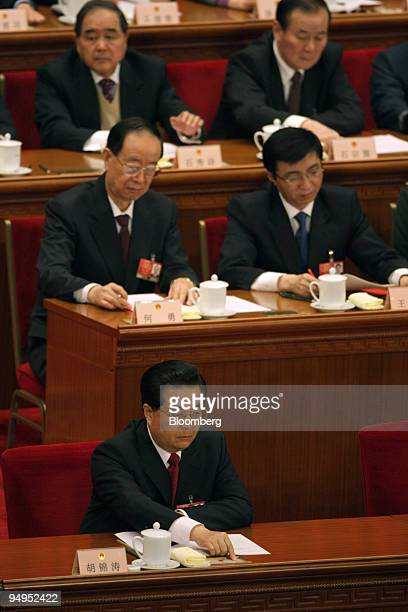Hu Jintao China's president bottom pushes a button signifying his vote at the closing ceremony of China's National People's Congress at the Great...