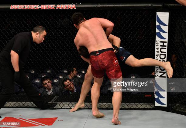Hu Yaozong of China attempts to secure a guillotine choke submission against Cyril Asker of France in their heavyweight bout during the UFC Fight...