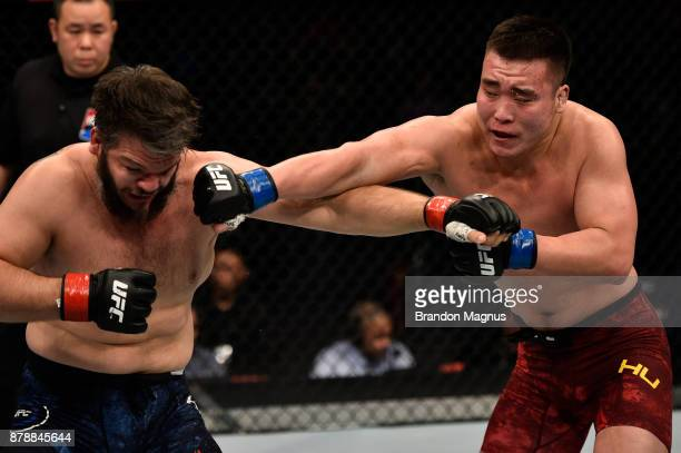 Hu Yaozong of China punches Cyril Asker of France in their heavyweight bout during the UFC Fight Night event inside the MercedesBenz Arena on...