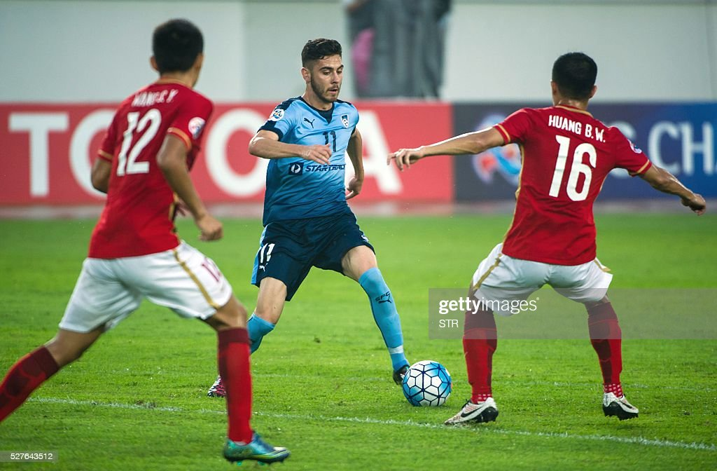 Huang Bowen (R) of China's Guangzhou Evergrande fights for the ball with Christopher Naumoff (C) of Sydney FC during their AFC Champions League group stage football match in Guangzhou, in China's Guangdong province on May 3, 2016. / AFP / STR